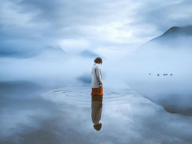 Girl standing in a lake surrounded by ripples and fog