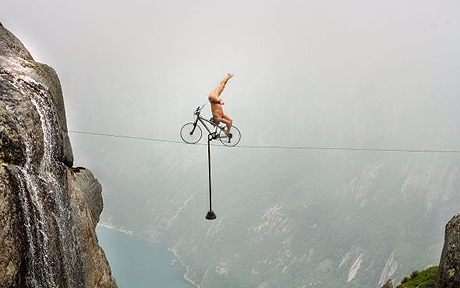 man riding a bicycle on a tightrope over a canyon