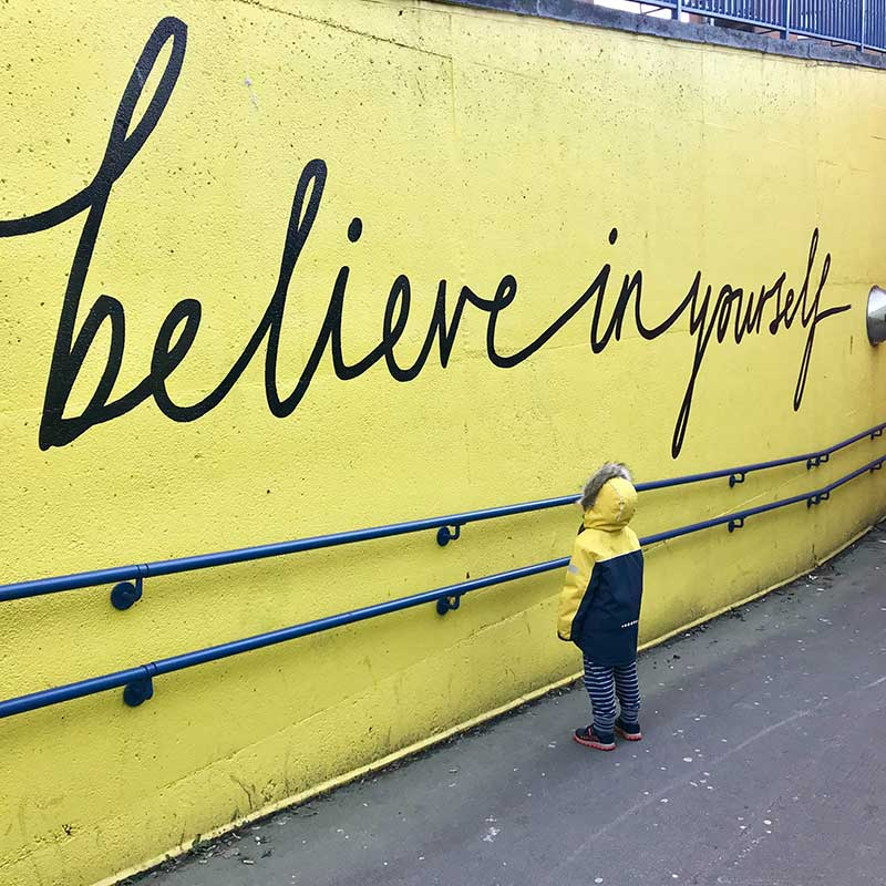 Believe in yourself written on a yellow wall | Self Esteem with NVC | photo by Katrina Wright on Unsplash