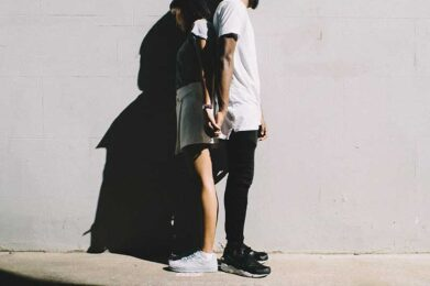 Young couple holding hands back to back | Building Relationships with NVC | photo by Henri Pham on Unsplash