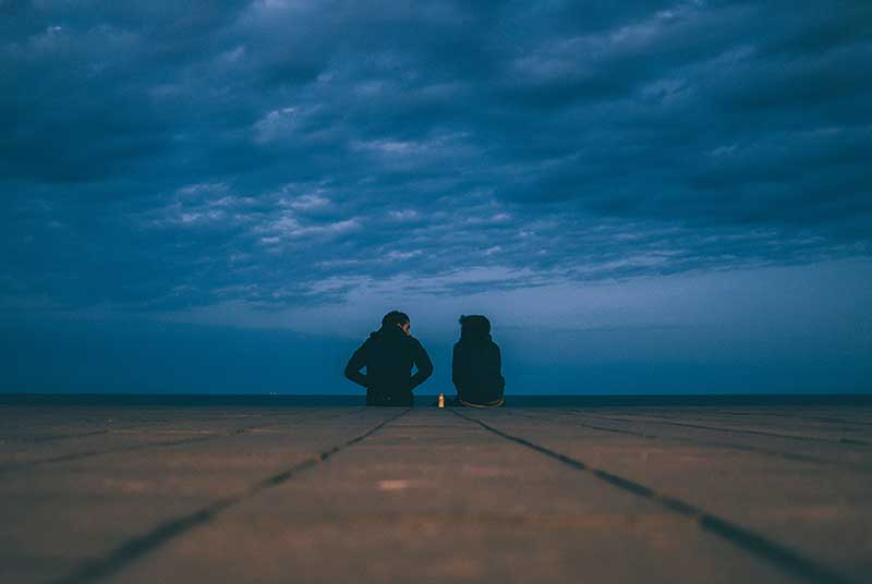 young couple seated on edge of dock | photo by Korney Violin on Unsplash