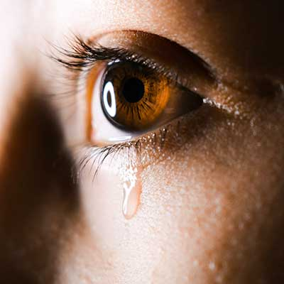 Loss and Grief closeup of teardrop falling from brown eye | Photo by Aliyah Jamous on Unsplash