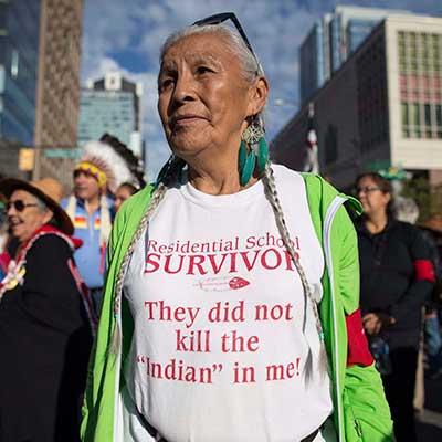 Indigenous elder wearing Residential School Survivor tee shirt