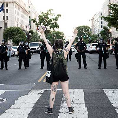 Black Lives Matter protester raising arms in crosswalk facing line of police officers